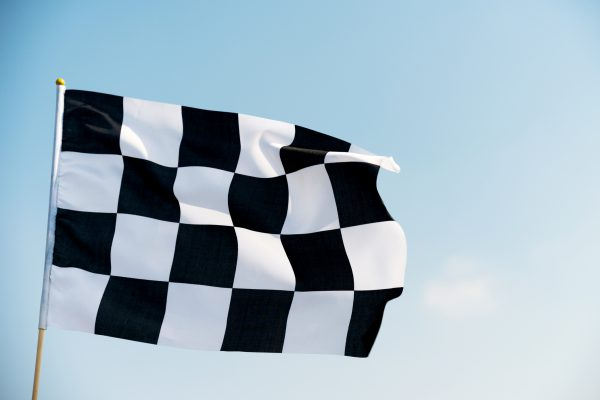Checkered flag flying on blue sky
